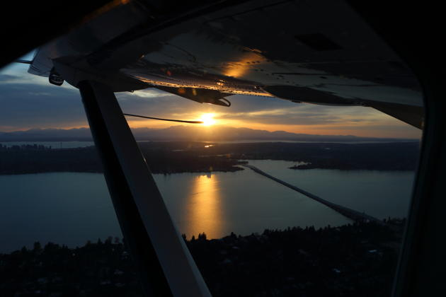 A great view from the Caravan cockpit of sunset reflecting from Lake Washington, with Seattle and the Olympic mountains in the distance.
